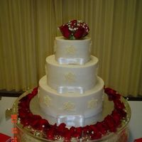 Miller_Wedding_Cake.jpg Off white wedding cake with snowflakes made from white chocolate; satin ribbon with bows attached around each tier. Fresh roses used on top...