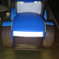 Tractor 3D sculpted New Holland grooms cake Covered in fondant. Tires are rice krispies covered in fondant.
