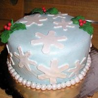 Christmas Cake 8 inch round cake covered in light blue Satin Ice fondant. Dusted cake with white luster dust. Snowflakes and pearls are fondant and holly...