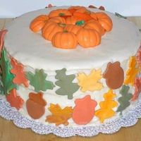 "Happy Thanksgiving White cake w/ buttercream frosting. Satin Ice leaves and acorns, choc. pumpkins on top of cake. (oops, buttercream was a bit ""runny.&..."