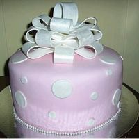 "Polka Dot Cake White cake w/ choc. pudding filling. Covered in Satin Ice w/ circles ""polka dots."" Pearls boarder and bow completes cake."