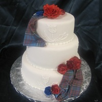 Tartan Cake ..for 10th anniversary. Scottish Thistle piped on the front. Tartan was scanned then printed on edible paper. Roses are gumpaste and royal...