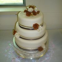 Brown/gold Shower All flowers are gumpaste. Satin ribbons. Lemon pound cake with strawberry filling covered in fondant.