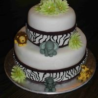 Jungle/safari Baby Shower  Cake covered in fondant with fondant animals and gumpaste flowers. Zebra stripes painted on with icing color. Got the great idea of using a...