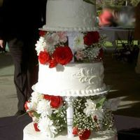 Red Roses For Jordan tiered cake with roses and other red flowers between layers and fleur de lis style scroll work on sides.