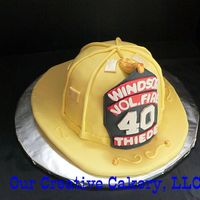 Fireman Helmet wasc cake covered with fondant. gumpaste emblem.
