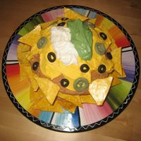 Plate Of Nacho's Cinco De Mayo cake-- Plate of nacho's. White cake with caramel filling. Olives, jalapeno's and tortilla chips are fondant, rest...