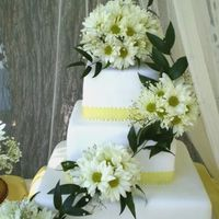 A Summer Of Daisies A 3 tier wedding cake that served 130 people. The cake was adorned with fresh daisies, the brides favorite flower. The top two tiers were...