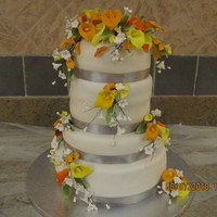 4 Tier Wedding Cake Fondant cake with gumpaste calle lillies airbrushed yellow and orange.