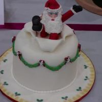 "Santa Popping Out Of A Cake   fondant covered 8"" round with fondant Santa figure ""popping"" out of the cake."
