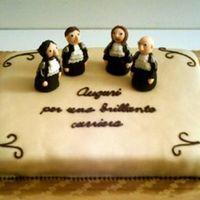 Italian Lawyers Grad Cake Choc cake covered with white choc plastic. Figures made from fondant. Writing says 'congratulations for a brilliant career'