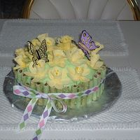 "Easter Flowers  Coconut cream cake with pineapple cheesecake filling;daffodils and butterfies are gumpaste and ""stems"" are chocolate covered..."