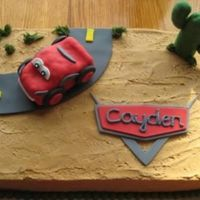 Cayden's Cars Cake Chocolate cake frosted in bc with fondant accents. Lightning McQueen is a fondant covered RKT. TFL!