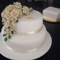 Ivory Roses Two tier mud wedding cake. Covered in ivory fondant with ivory sugarpaste roses.