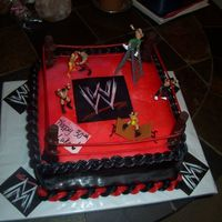 Wwe Chocolate cake with chocolate filling covered in MMF airbrushed black and red. Poles are solid chocolate, licorice strings, and toy WWE...