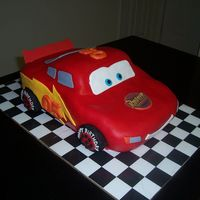 Lightning Mcqueen White Cake covered with MMF. Decorations are fondant and edible images.