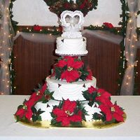 Christmas Wedding  Draped buttercream consisting of a base of three 10-in cakes, a 14-in, and topped with another 10-in. The bride's silk poinsettias...