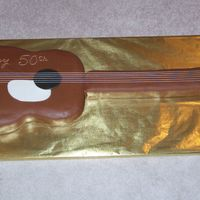 Bill's 50Th   4 ft long chocolate fondant covered guitar cake. Strings and their connections were not edible.