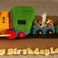 "Lennox's 1St Birthday Cake An almond pound cake, with 2 carriages. Chocolate ""flake"" bars for logs and lollies for cargo."