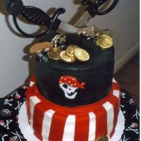 Skulls And Bones STACKED ROUND CAKES, BC ICING, RED FONDANT STRIPES, AIR BRUSH BLACK, SKULL TOMATCH MATERIAL COVERED BOARD, CHOC. COINS, DOLLAR STORE SWORDS...