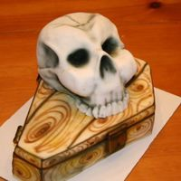 Coffin & Skull The skull is sculpted from the Wilton Sportsball pan. The coffin is a two layer 1/4 sheet cake. Both are covered in MMF and airbrushed with...