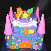Castle Cake A castle cake done in Dora colors. Buttercream icing with MMF decorations. PVC pipe and ice cream cone towers covered in MMF. TFL