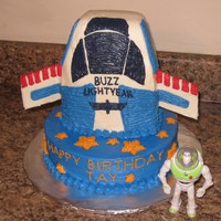 Buzz Lightyear Rocketship 10 inch round. 1/4 sheet cake cut to form rocketship. Wings made of cake board (greaseproof) and covered with frosting.