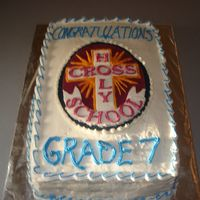 Grade 7 Grad Chocolate cake with Twinkie filling. Buttercream frosting. Holy Cross emblem made out of fondant.