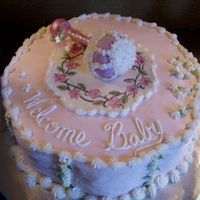 "Welcome_Baby This is a 12"" buttercream iced baby cake. The rattle was a carved cupcake with a gumpaste handle. The plaque was made of white..."