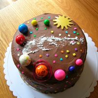 Solar System Cake chocolate cake with cookie and cream filling. The planets are gumballs, the sun is a chocolate transfer and the Milky Way is made with...