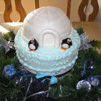 Igloo Cake Cake covered in fondant and penguins also fondant. Brushed with edible glitter.