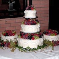 Fall Wedding Cake With Fresh Fruit Cakes are covered with Choco-Pan (blanc). Swags are 50/50 gumpaste/chocopan and vertical lines are buttercream. Cakes were topped with...