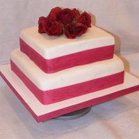 "Square Cake With Roses it's a 2 tier cake using 8"" and 10"" square cake pans. The cake is vanilla and I covered it with fondant and used ribbon and..."