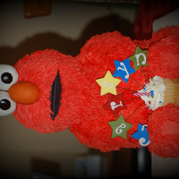 "Elmo Made for a 2nd. Birthday. Head is ball pan body is wonder mold sitting on an 8"" cake. Arms, legs, eyes, and nose are RKT. I found the..."