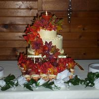 Autumn Wedding Cake This was for my uncle's 3rd wedding. 2 tiered cake with 48 cupcakes bellow. BC icing with artificial leaves on side of cake, topper is...
