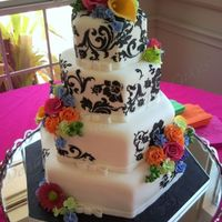 Black Damask With Bright Flowers This four tier hexagon cake was covered in homemade white chocolate fondant and then stenciled with black royal icing. The bright colored...