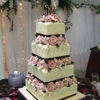 Pink Flowers And Cherry Blossoms 6 8 10 12 inch square cakes with Gumpaste flowers between the tiers. Cake topper is a sugar letter N. Fondant covered cakes with...