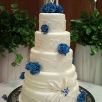 "Blue Roses Wrapped With A Bow This fondant covered cake features blue gumpaste roses, lace wraps, a drape wrapped around one tier with a bow. 6"" 8"" 10"" 12..."