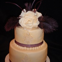 Michelle   Ivory buttercream with fleur de lis, gardenia and eggplant feather topper