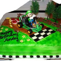 Mario Kart Luigi Birthday Cake The Luigi figure is a toy figurine, the fence and trees are plastic pieces. The bananas, shells, and stars are all made from fondant. This...