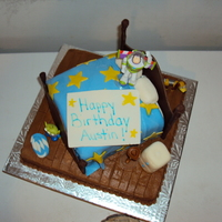 "Toy Story Themed The bottom cake is covered with buttercream, The ""bed"" is covered with MMF, the accents are MMF as well."