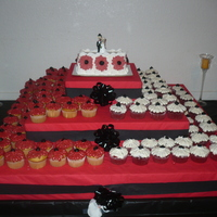 Wedding Cupcakes!   Cream filled cup cakes with red and white buttercream flowers. Top cake is ice cream cake.