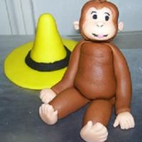 Curious George   curious george and yellow hat made of fondant.
