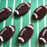 Football Brownies Brownies cut out with a football shaped cookie cutter. Decorated with buttercream icing.