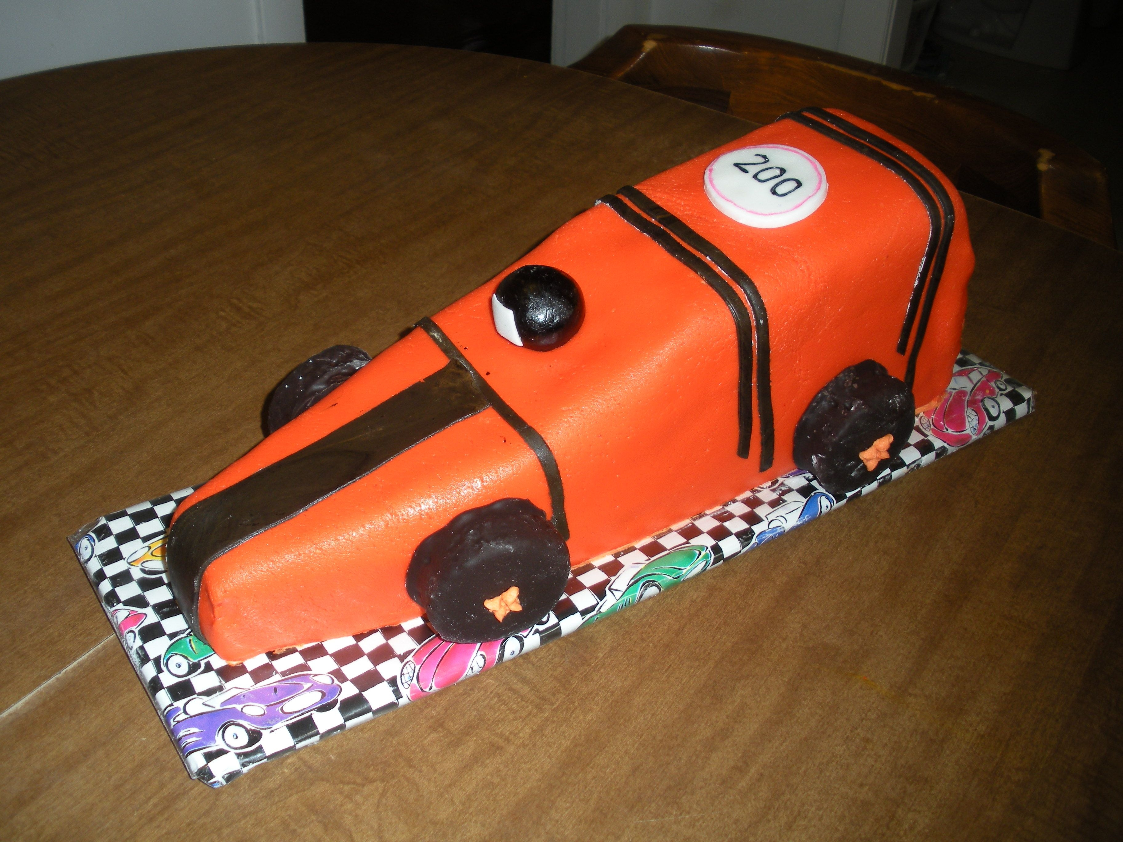 Race Car  yellow pound cake covered in buttercream and then marshmallow fondant with fondant features.. the humidity helped with making the car shiny...