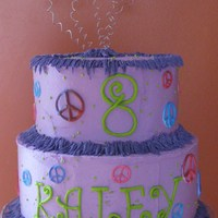 Peace Kaley Covered in buttercream with royal icing peace signs and writing. Fringe is buttercream