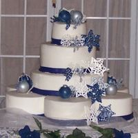 "Winter Wedding  The cake is iced in buttercream 6 8"" cakes on the bottom, 14,10 and 6"" stacked. Ribbon is mmf, snowflakes and ornaments are white..."