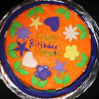 "Purple And Orange Cake 2 layer chocolate cake, one 10"" and one 8"", frosted with violet and orange frosting. Decorated with fondant flowers."