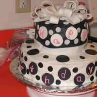 Black & White Birthday Cake Two tiered cake with buttercream frosting and fondant black & white dots. Bow is fondant.