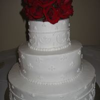 White Scrolls   I did alright for not favoring working with BC on this wedding cake. Bride provided picture of cake desired. Simple scrolls.